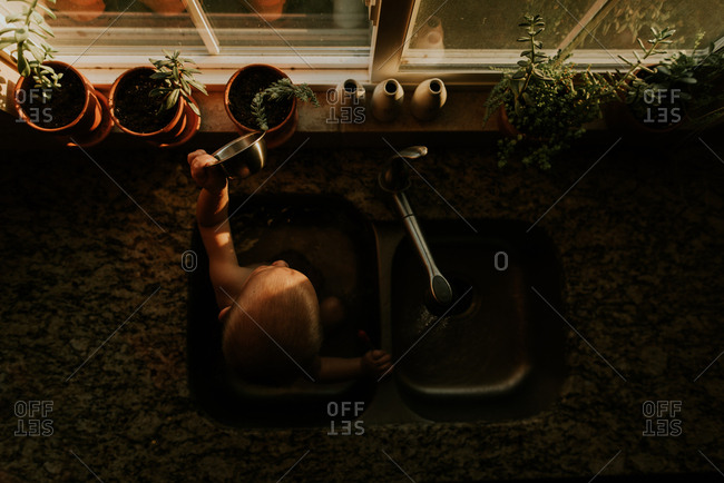 Boy watering potted plants while bathing in kitchen sink