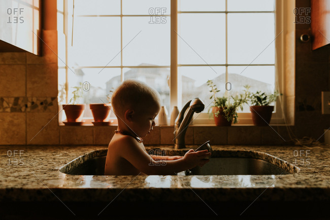 Boy sitting in kitchen sink with a bowl