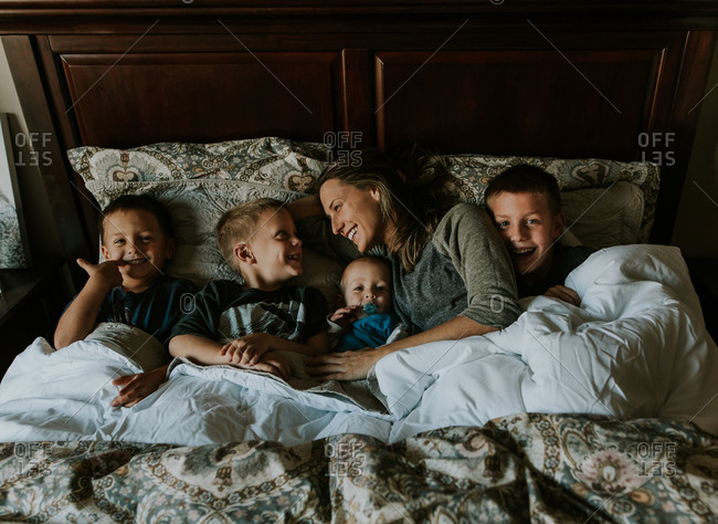 Mother and four boys lying in bed