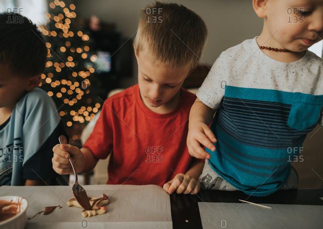 Boys decorating Christmas cookies