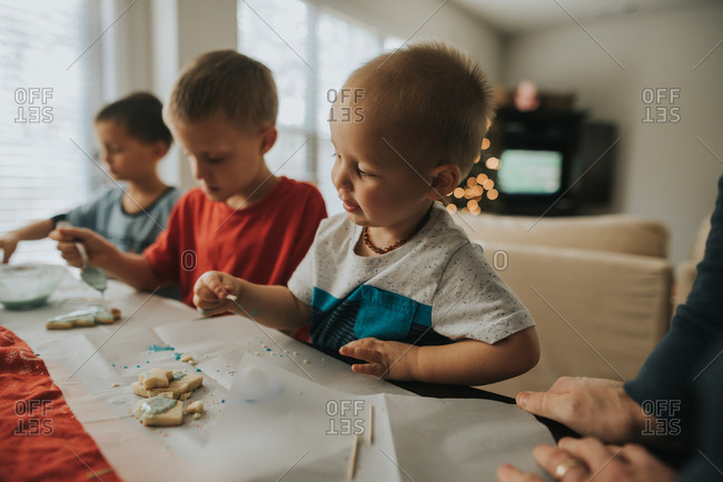 Three boys decorating Christmas cookies