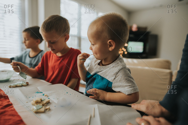 Baby tasting frosting while decorating Christmas cookies with brothers