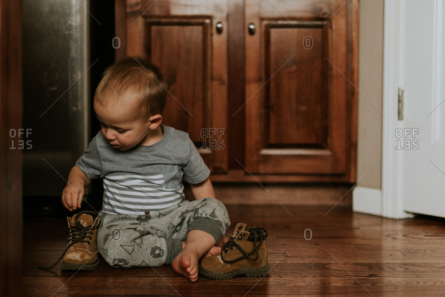 Baby boy playing with boots on floor