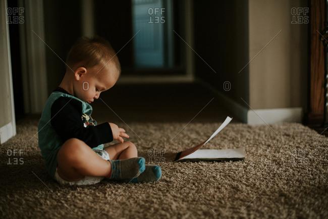 Baby boy sitting on carpet