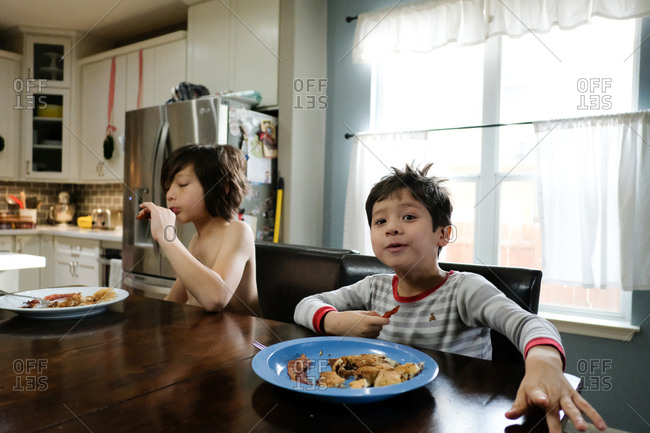 Two boys eating breakfast at kitchen table
