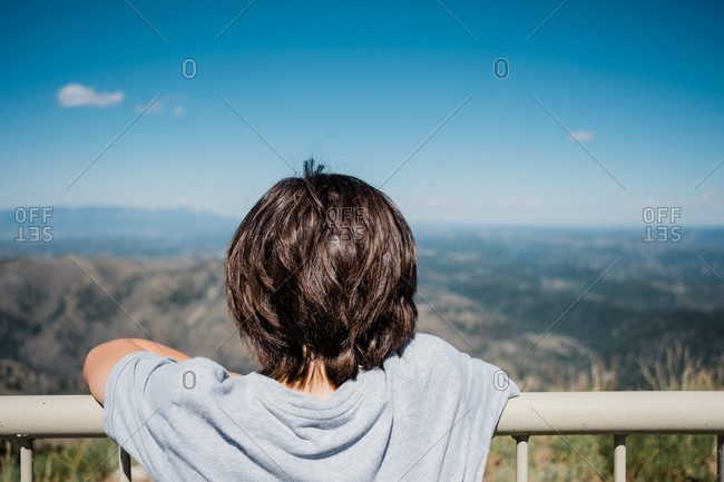 Rear view of boy overlooking mountain landscape