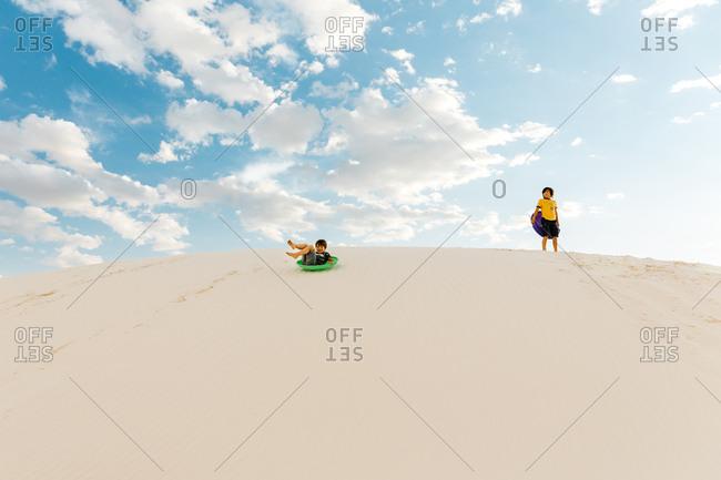 Kids sledding down on hills at White Sands National Monument