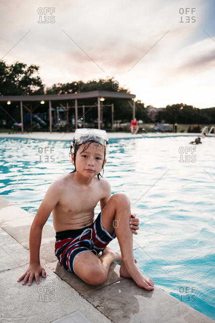 Young boy wearing goggles sitting on edge of swimming pool