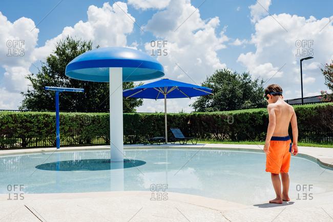 Boy walking into shallow swimming pool