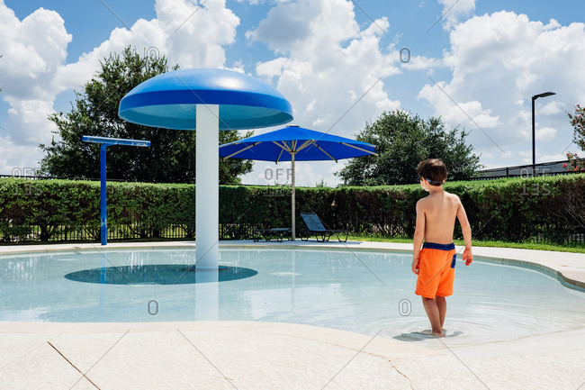 Young boy walking into shallow swimming pool