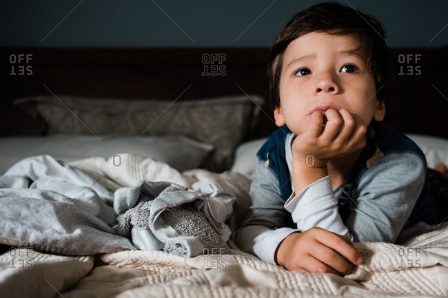 Little boy sitting on bed looking away