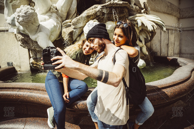 Austria- Vienna- group of three friends taking a selfie in front of fountain at Hofburg Palace
