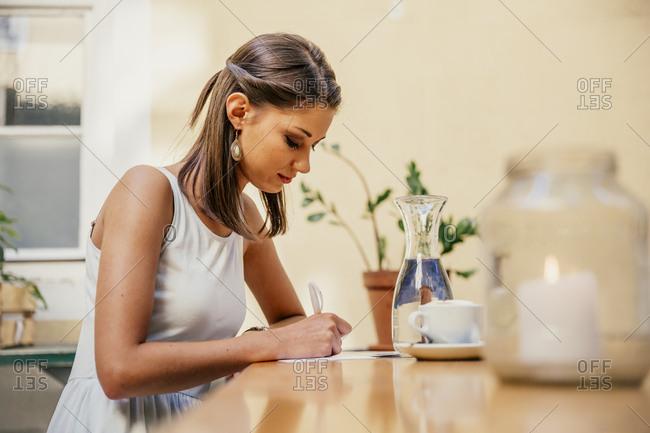 Austria- Vienna- Young woman sitting in Heurigen restaurant writing postcards