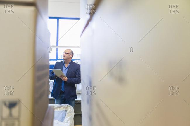 Businessman checking goods receipt in storehouse