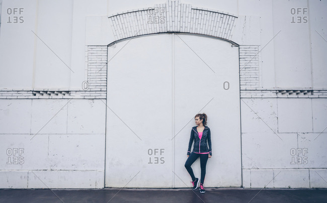 Woman wearing sports wear standing in front of white door