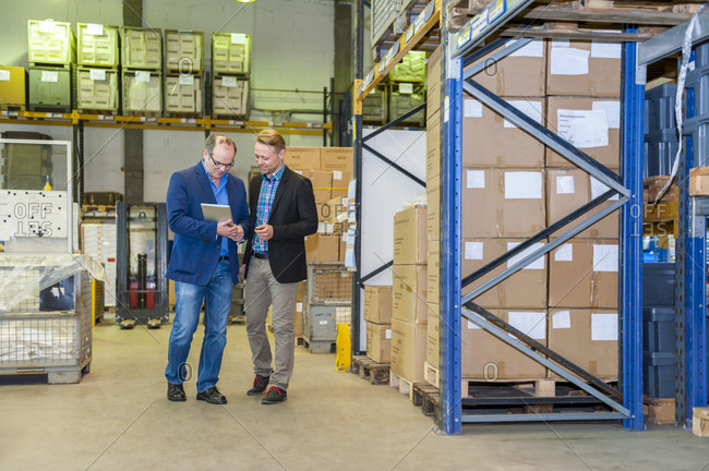 Two managers discussing packaging and shipment in storage hall