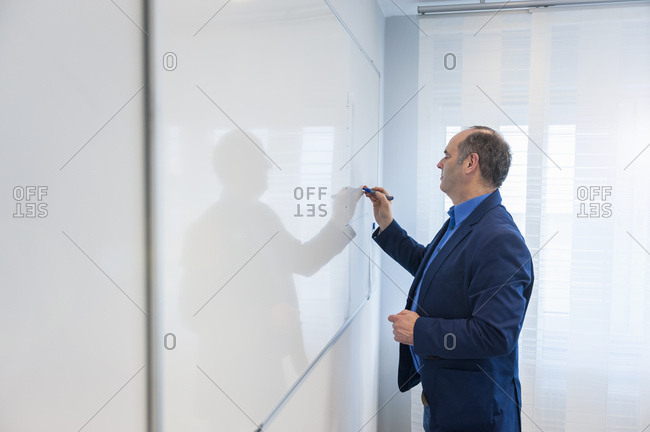 Manager in office writing on white board