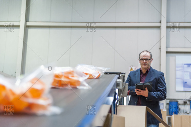 Manager checking packaging of goods in plastics factory