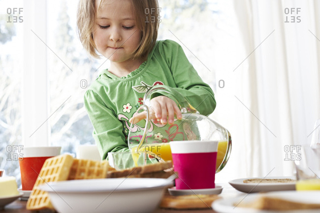 Portrait of little girl pouring orange juice into a glass
