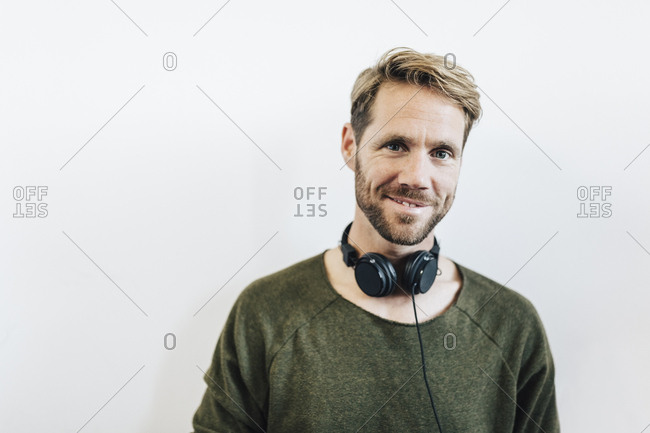 Portrait of smiling man with headphones against white background