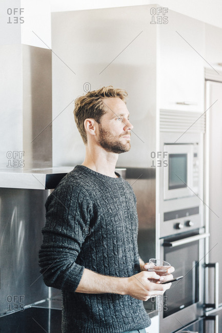 Pensive man standing in kitchen with cell phone and glass of water
