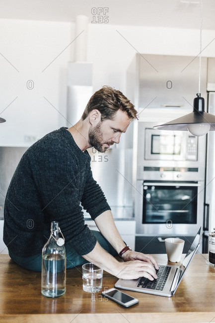 Man sitting on worktop in the kitchen using laptop
