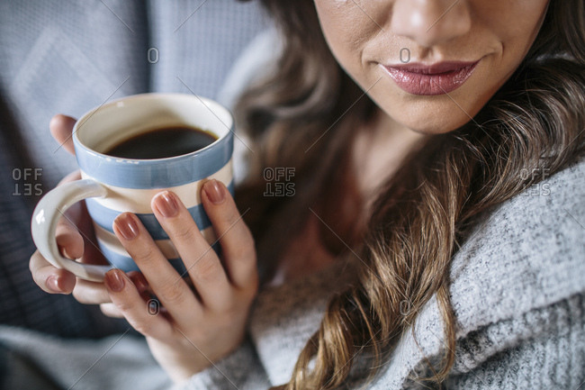 Young woman at home with cup of coffee