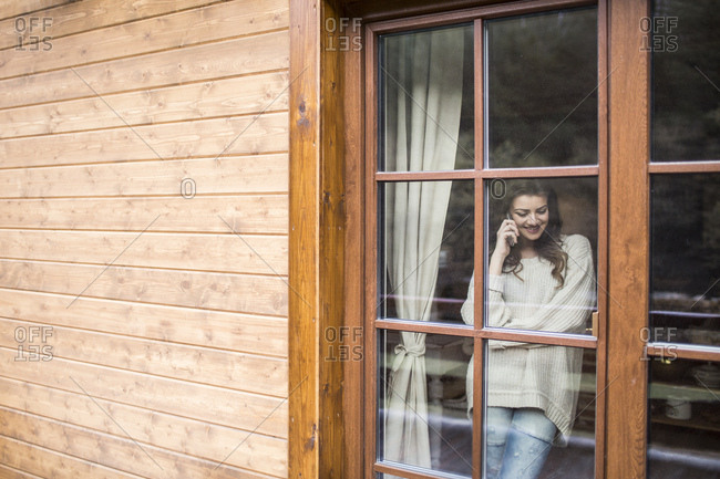 Young woman standing at the window using smartphone