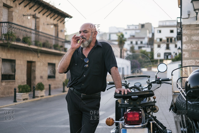 Spain- mature man smoking next to motorcycle with a sidecar