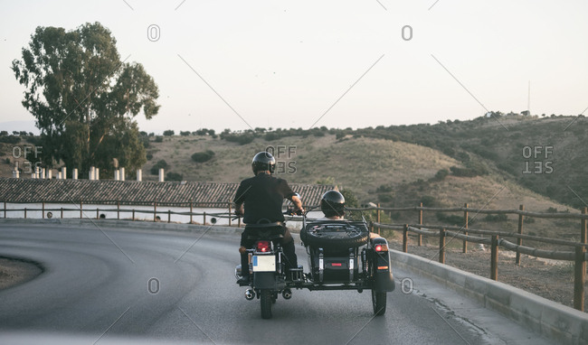 Spain- mature couple riding on motorcycle with a sidecar