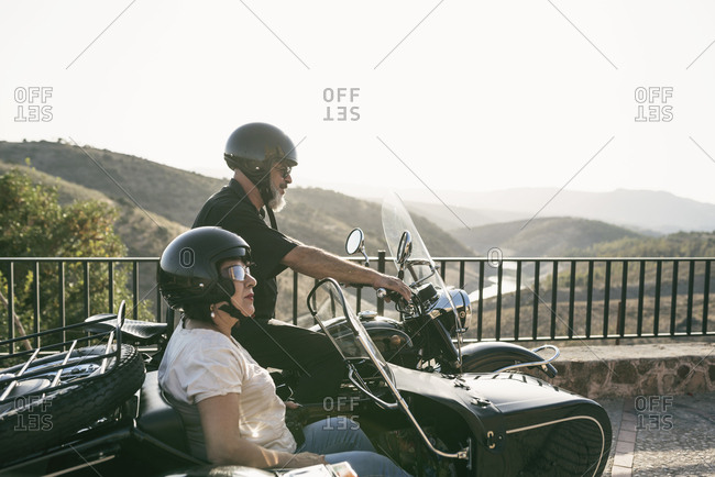 Spain- mature couple on motorcycle with a sidecar on a bridge