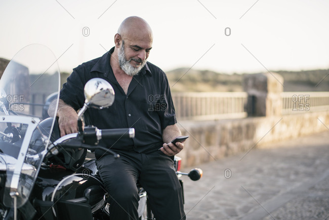 Spain- mature man on his motorcycle with a sidecar looking at cell phone