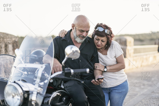 Spain- mature couple with motorcycle with a sidecar looking at cell phone