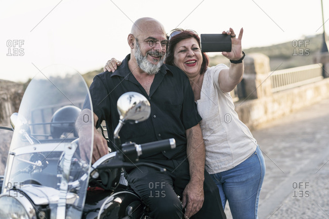 Spain- mature couple with motorcycle with a sidecar taking a selfie