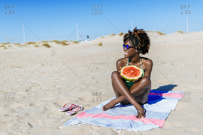 Happy young woman with watermelon on the beach