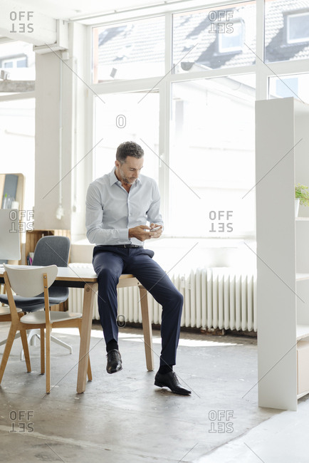 Businessman in office looking at cell phone