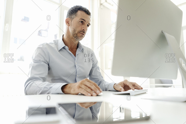 Businessman using computer at desk in office