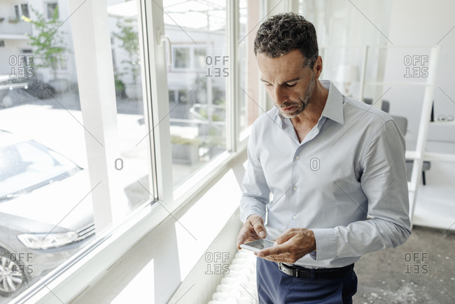 Businessman in office at the window looking at cell phone