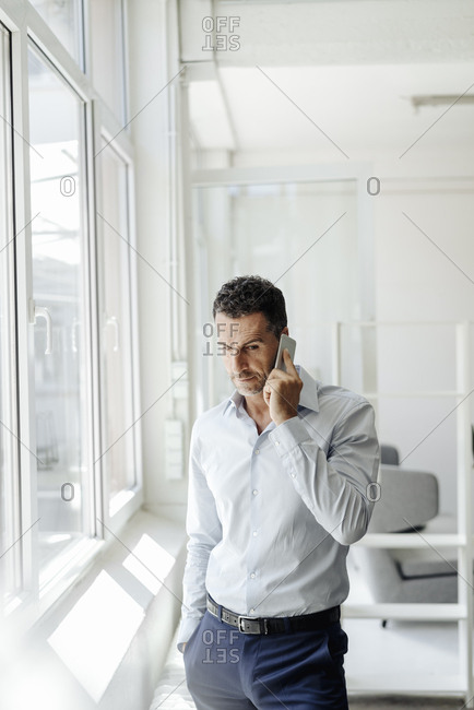 Businessman at the window in office on cell phone
