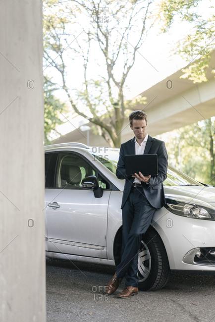 Businessman standing next to car using laptop