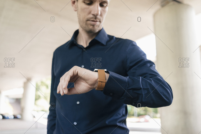 Businessman standing at underpass checking the time