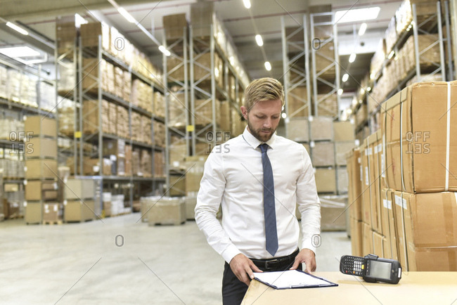Businessman with clipboard and barcode scanner in warehouse