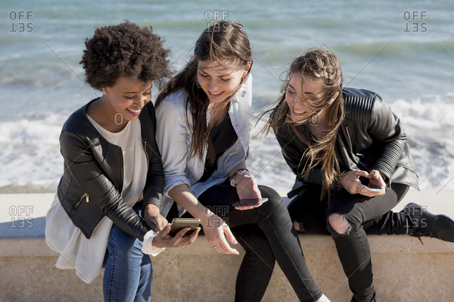 Three young women sitting on wall looking at smart phone