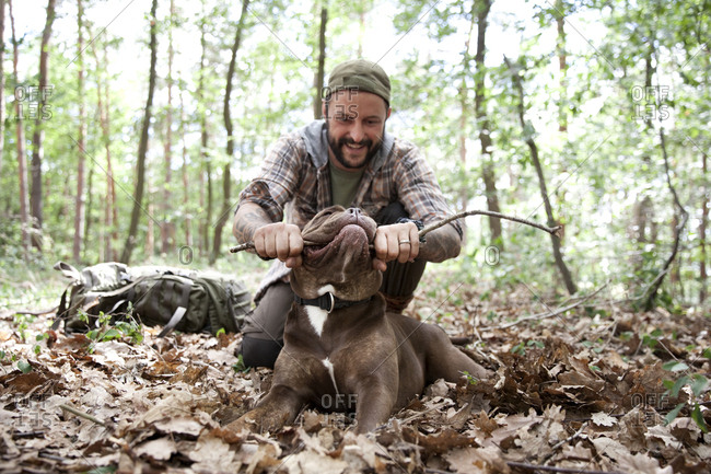 Man playing with dog in forest