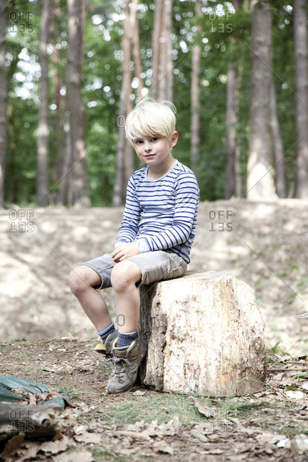 Boy in forest sitting on tree stump