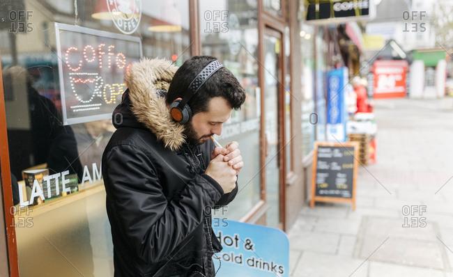 UK- London- man with headphones standing in front of window display lighting a cigarette