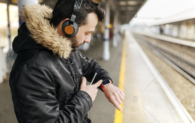 Man with headphones standing on platform looking at his smartwatch