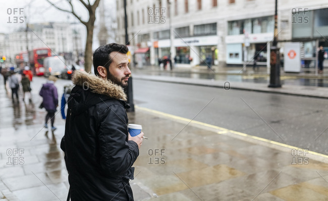 UK- London- man with coffee to go on a rainy day