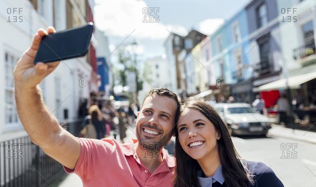 UK- London- Portobello Road- happy couple taking selfie with cell phone