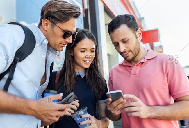 UK- London- Portobello Road- three  friends looking at cell phone
